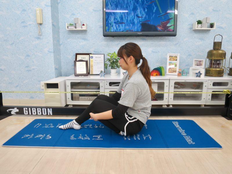 床に座り脚を持ち上げる